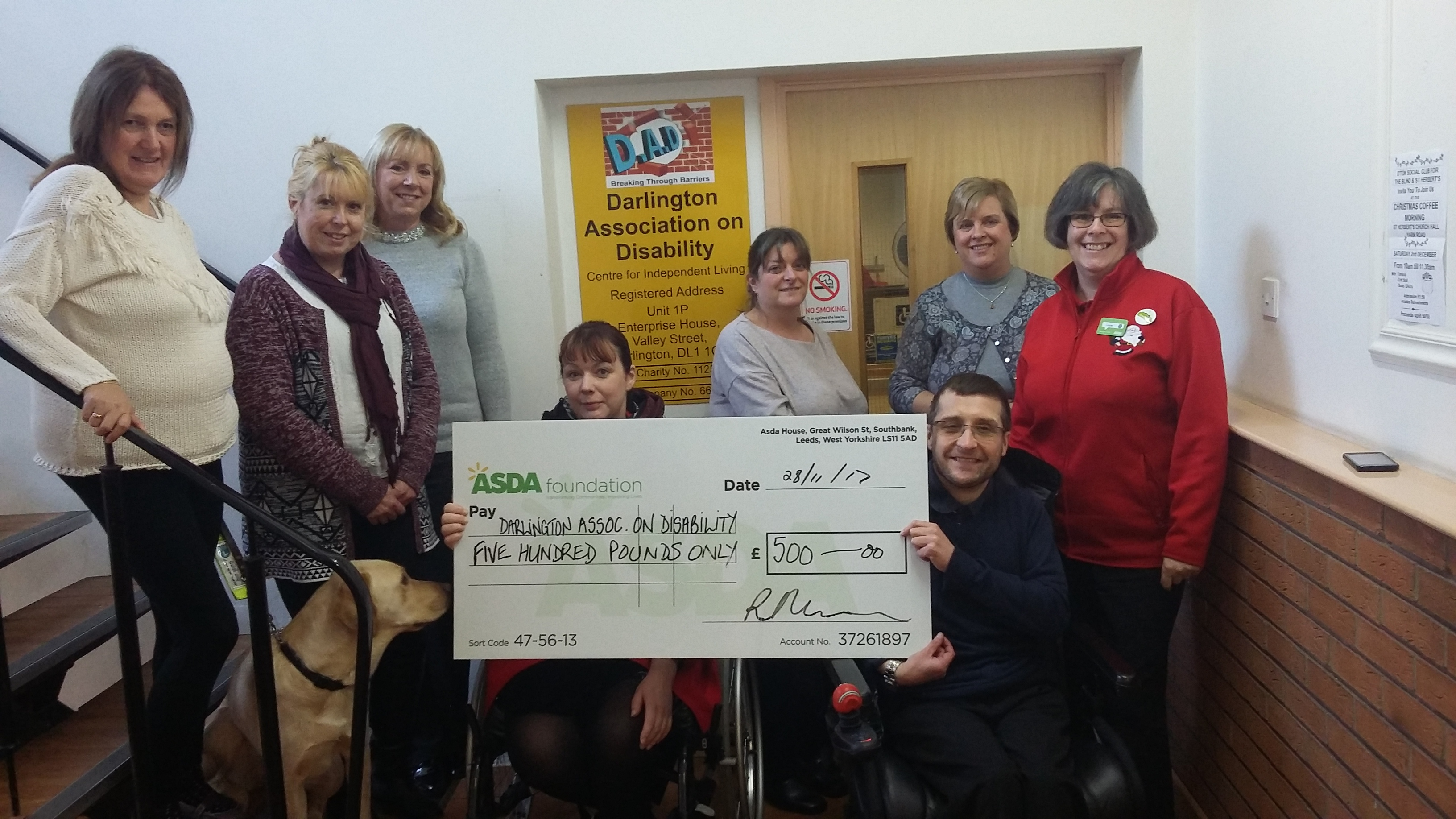Photo shows Conor Curwen and staff members receiving the cheque from Louise Gibson outside DAD's office entrance