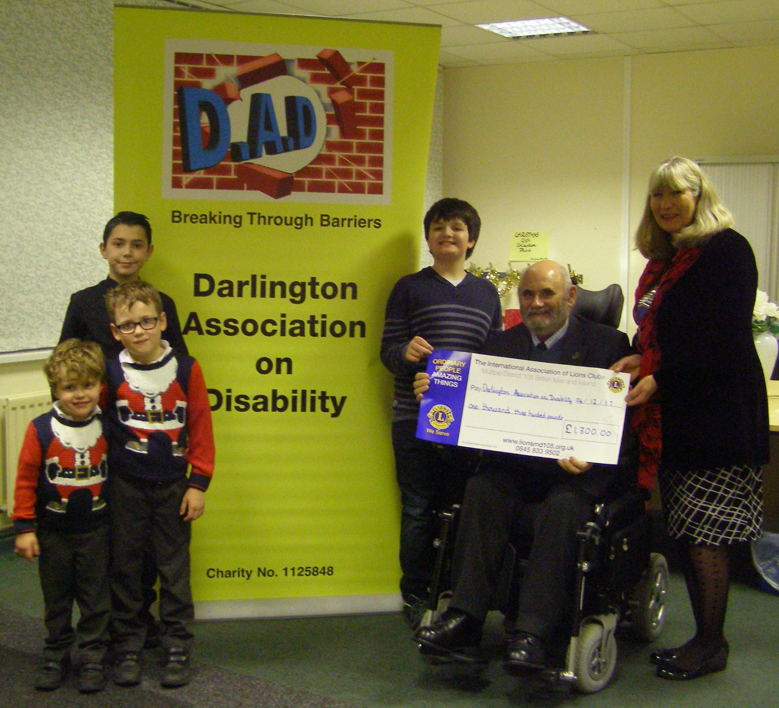 Photo showing Jenny Lumley presenting a cheque to Gordon Pybus aided by Alfie,Oscar, Vinnie and Ethan